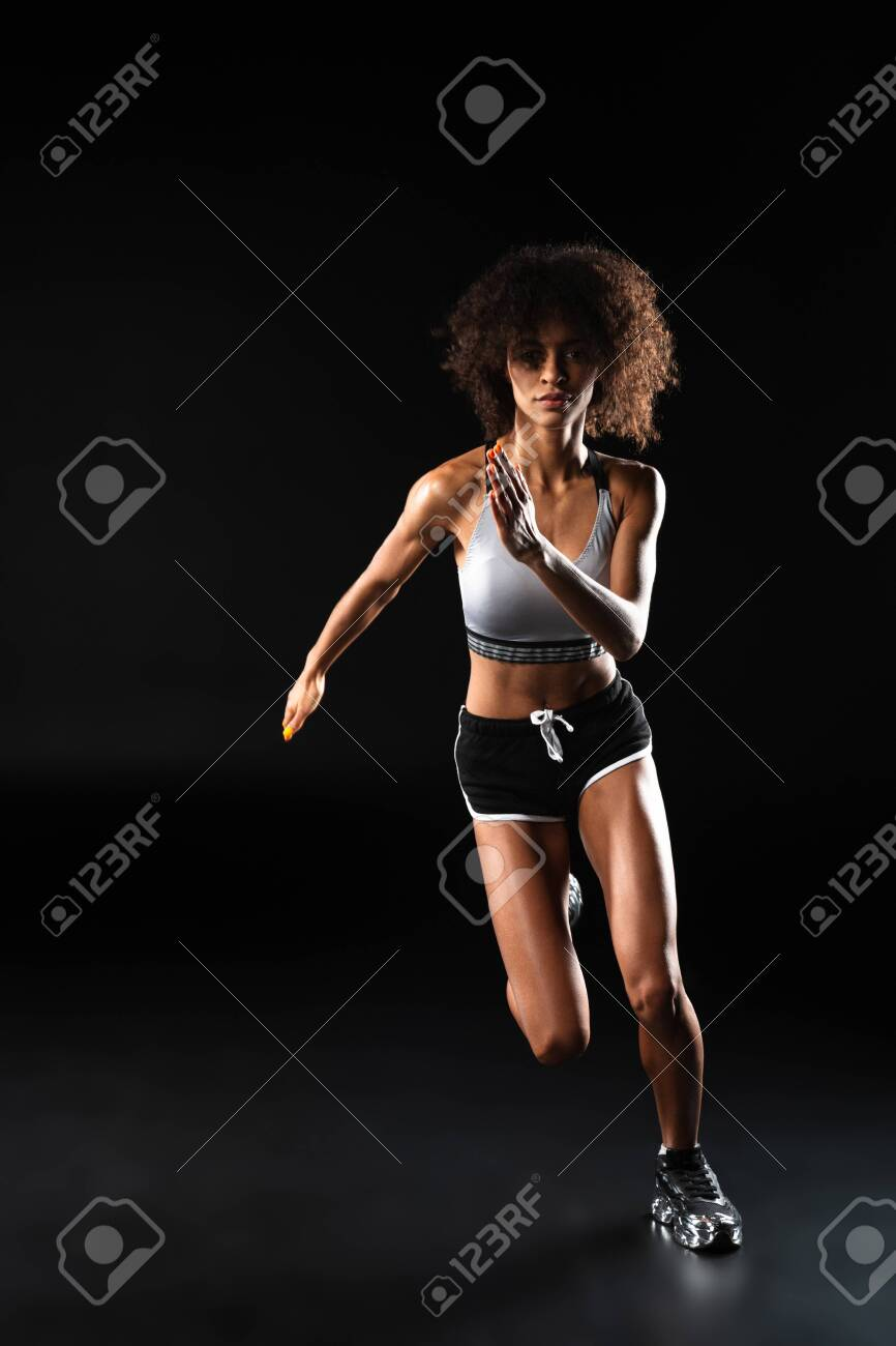 Image of focused african american sportswoman doing exercise while working out isolated over black background - 144494078