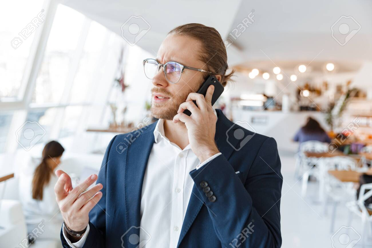 Image of handsome serious concentrated young businessman indoors in office talking by mobile phone. - 146485802