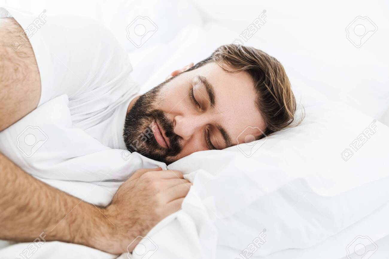 Image of young unshaven caucasian man sleeping alone in bed with white linen at home - 148002674