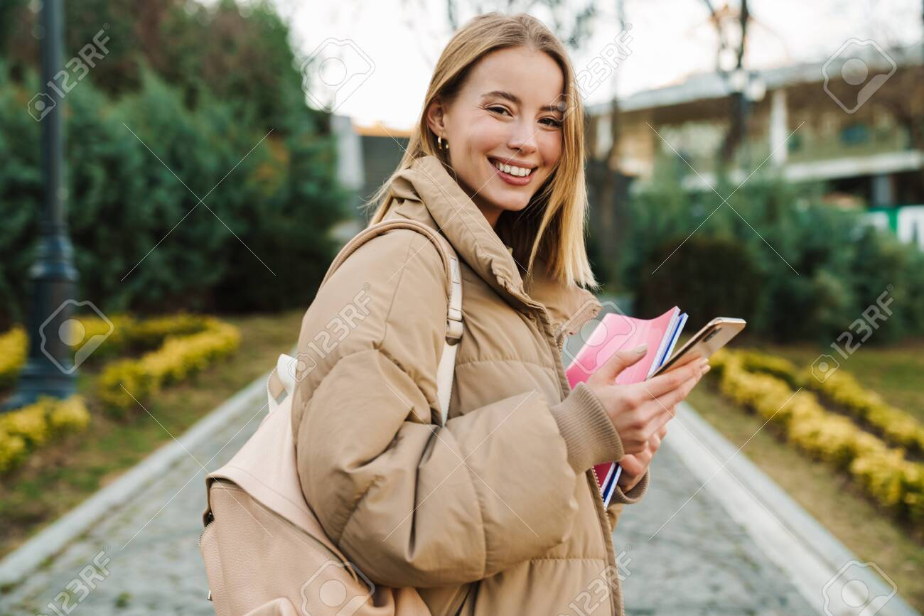 Portrait of smiling young woman holding exercise books and using mobile phone while walking in park - 148360425