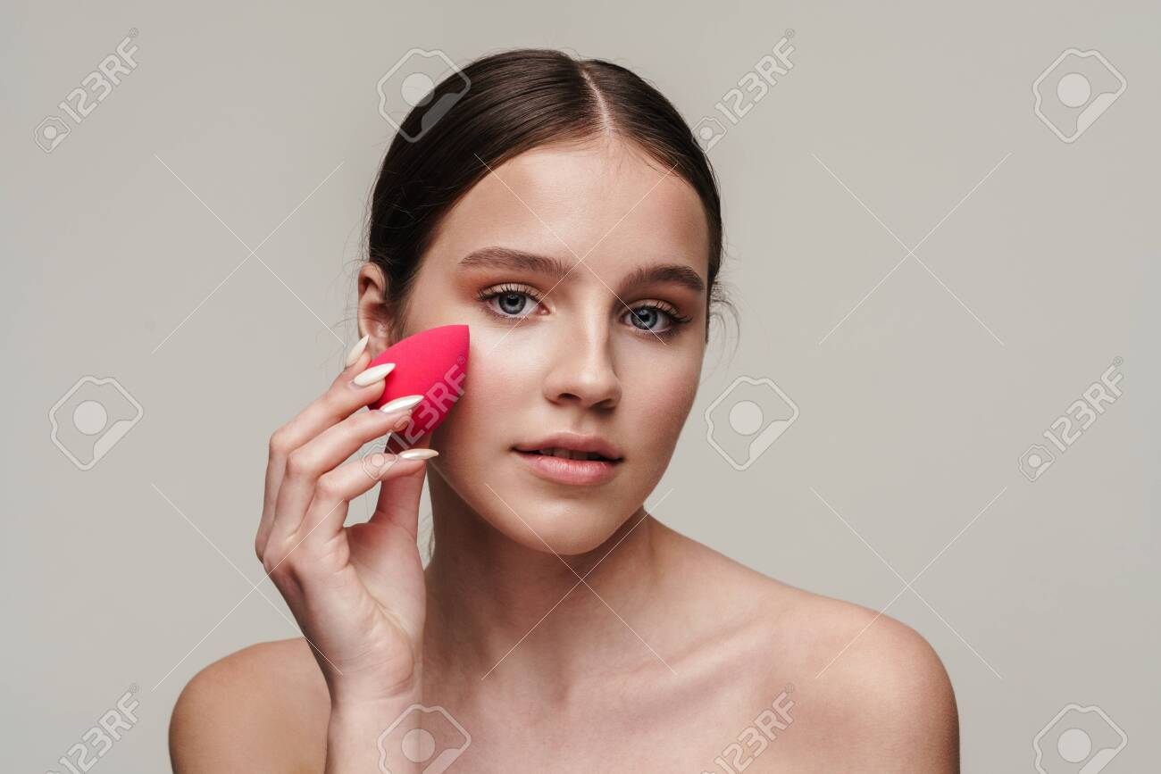 Image of beautiful shirtless woman using makeup sponge and looking at camera isolated over grey background - 148849066