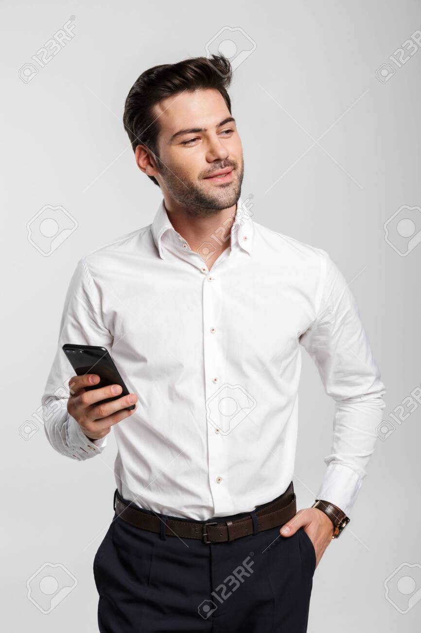 Image of young serious businessman holding and using laptop isolated over white background - 150802789