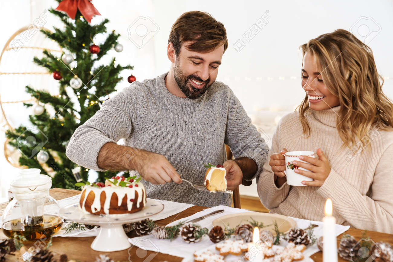Charming cheerful couple eating pie while having Christmas dinner in cozy room - 165073246
