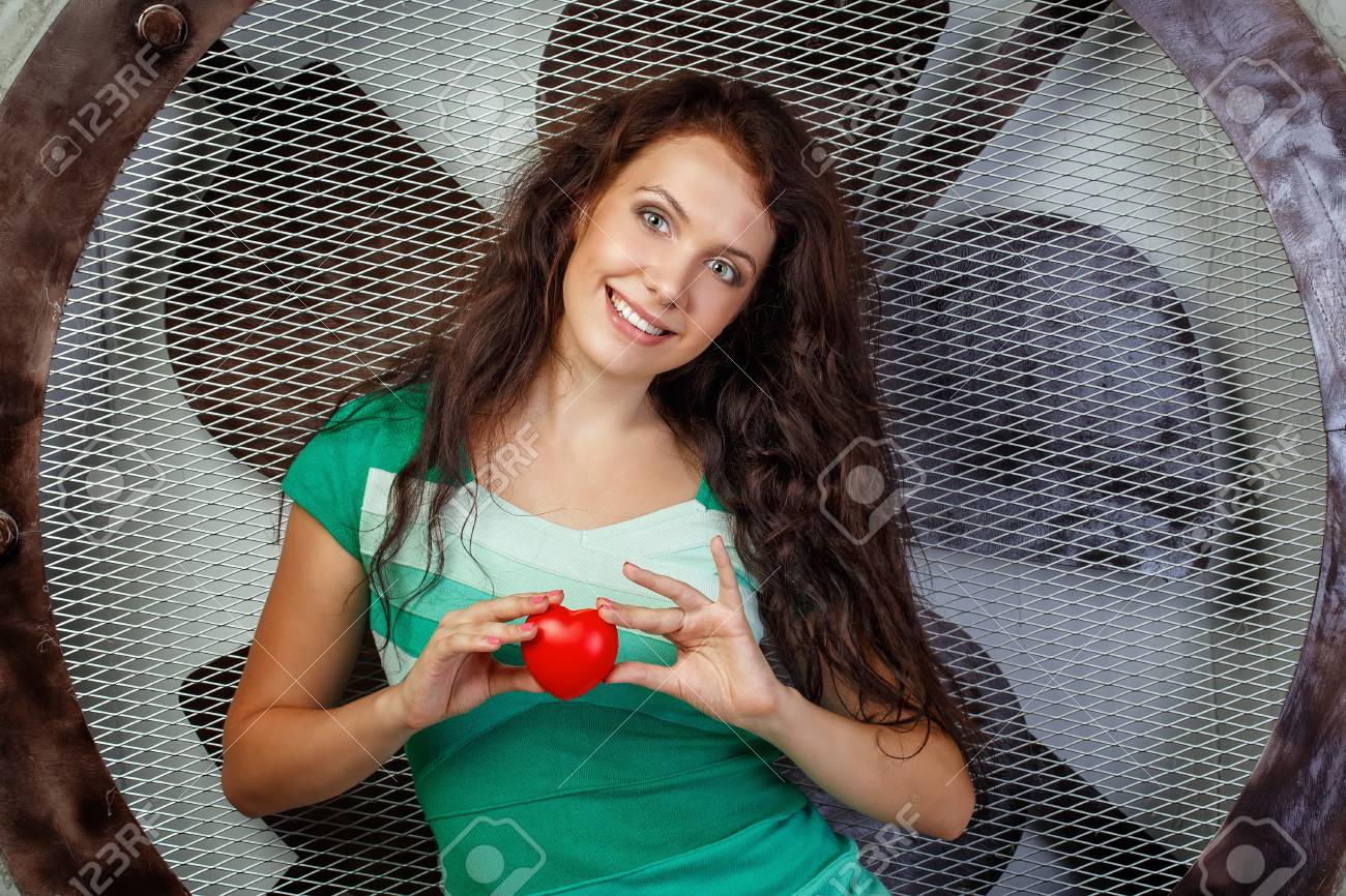 Beautiful girl in a dress holding a heart, photographed in the studio Stock Photo - 21752448
