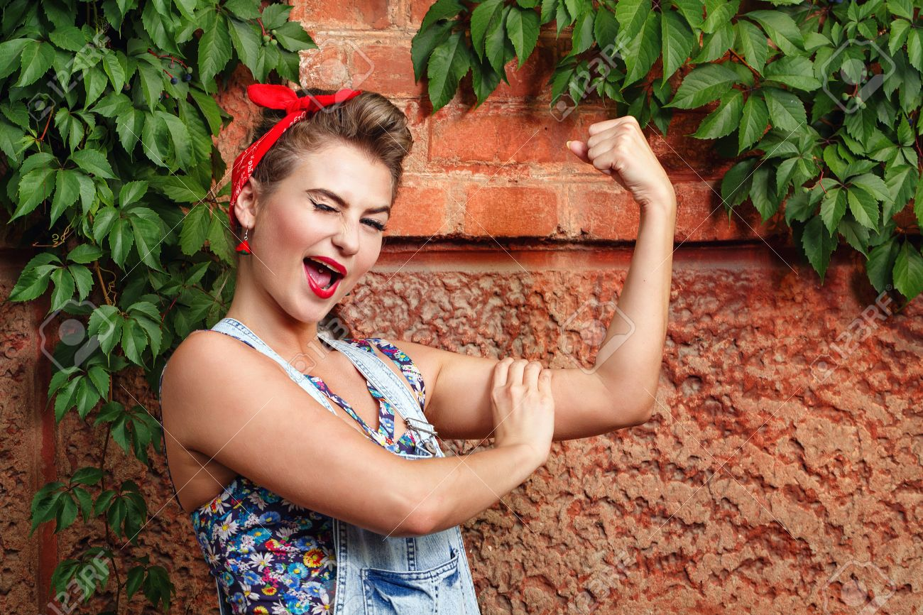 Beautiful pin-up girl in denim overalls and a red bandana  winks and demanstriruet bicep Stock Photo - 22479911