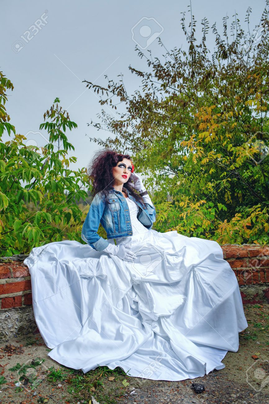 b07c1df6a156 Beautiful bride in wedding dress and denim jacket in autumn park Stock  Photo - 24916778