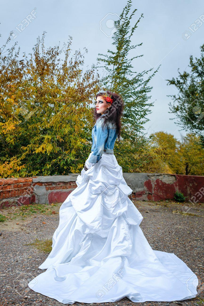 Schöne Braut im Hochzeitskleid und Jeansjacke im Herbst Park