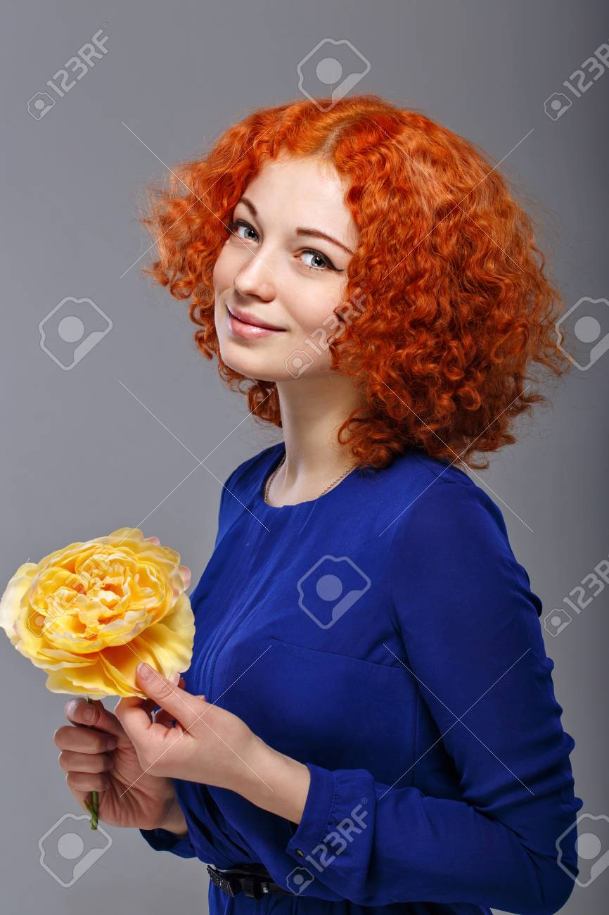 Attractive young red-haired girl in a blue dress holding in her hands a  yellow d4a102b00