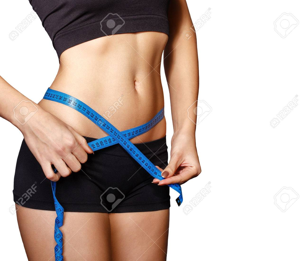 Fit and healthy young lady measuring her waist with a tape measure in centimeters and millimeters. She has her black gym exercise outfit on. Isolated image on white. - 36586653
