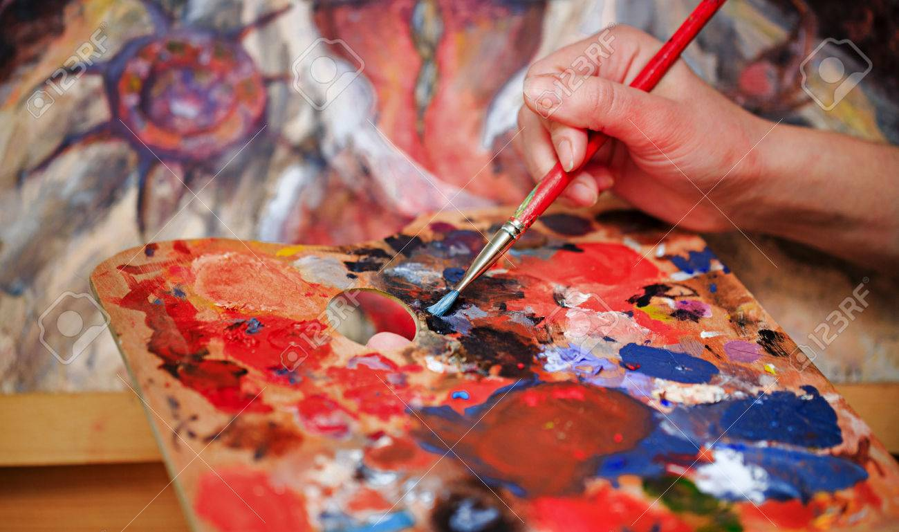 Artist brush mix color oil painting on palette is holding in his hand closeup - 38000805