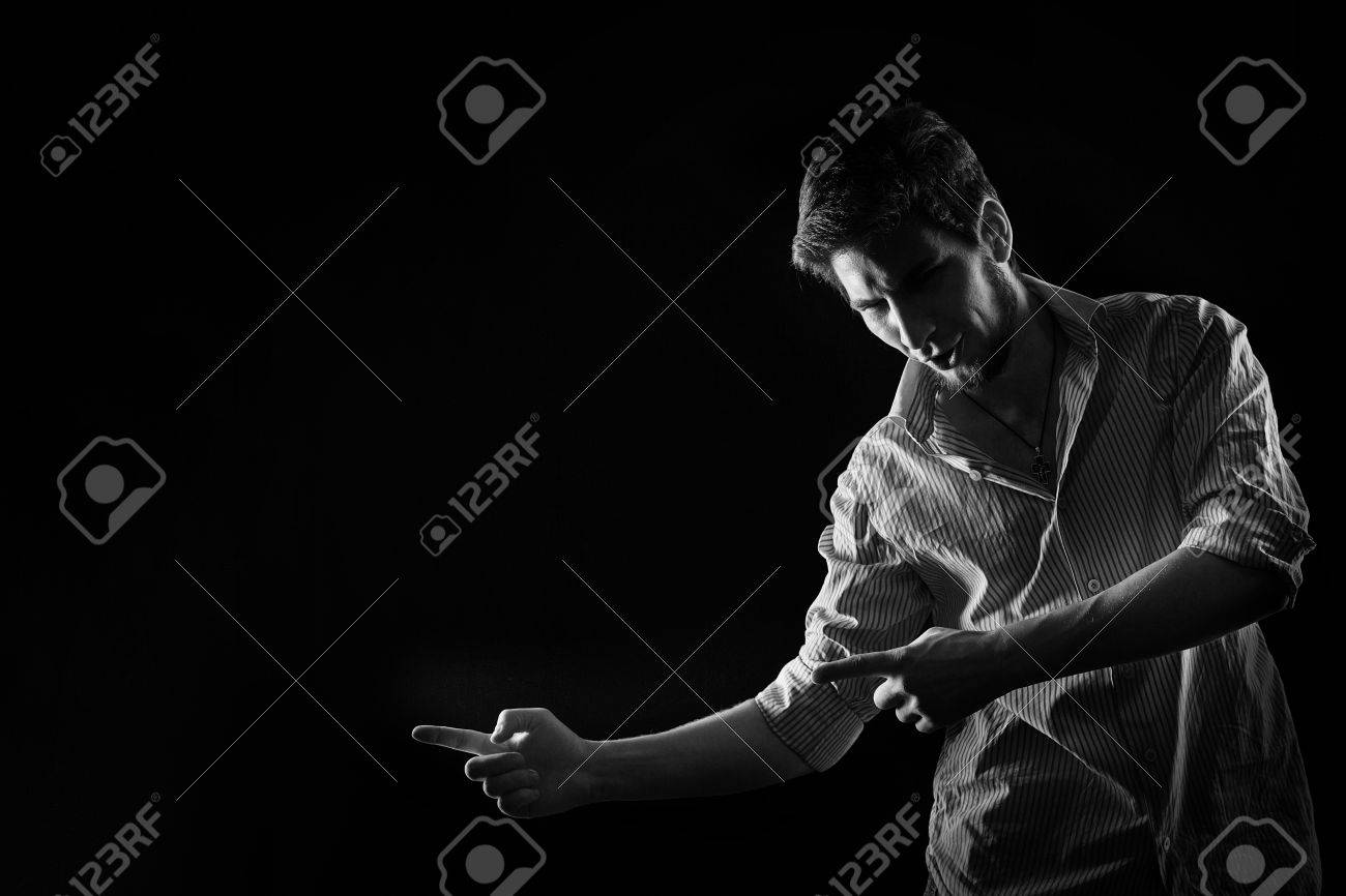 Dramatic portrait of a young man in shirt and jeans shot in the studio in black and white style low key a man shows his index fingers in motion