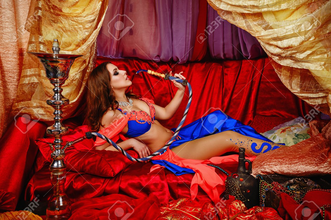Sexy oriental beauty is in the tent on cushions and smoking hookah. The concept of the Arab harem. - 39818264