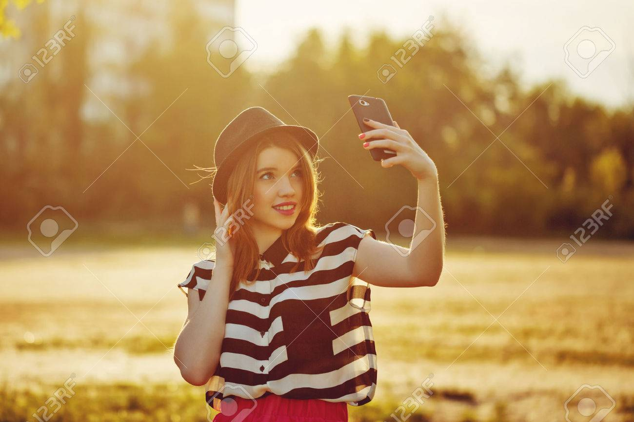 Young attractive girl in the hat makes self on a cellphone. The concept of urban street youth fashion. Communication in social networks. - 40384872