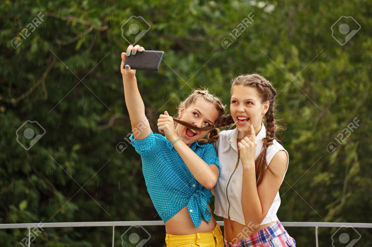 Best girlfriends teenagers being photographed in a summer park. Photo phone selfie. Girls dressed in shorts and a shirt. On summer vacation. The concept of true friendship. - 43213227