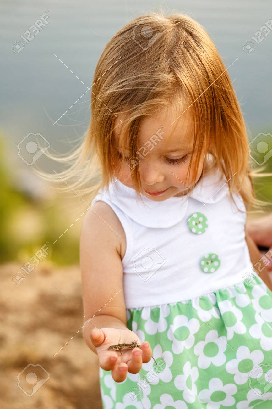 Little girl holding a green lizard on his arm i am learning concept of the