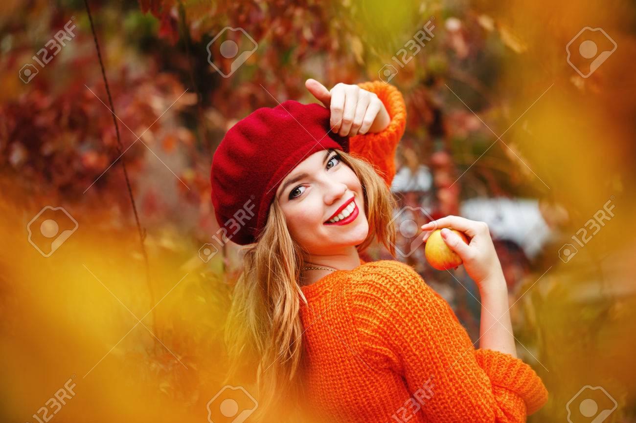 La Jolie Fille De L Air jolie fille dans un béret et un pull dans le parc de l'automne, la tenue  d'une pomme mûre. fille appréciant l'air frais. la jeune fille de sourire