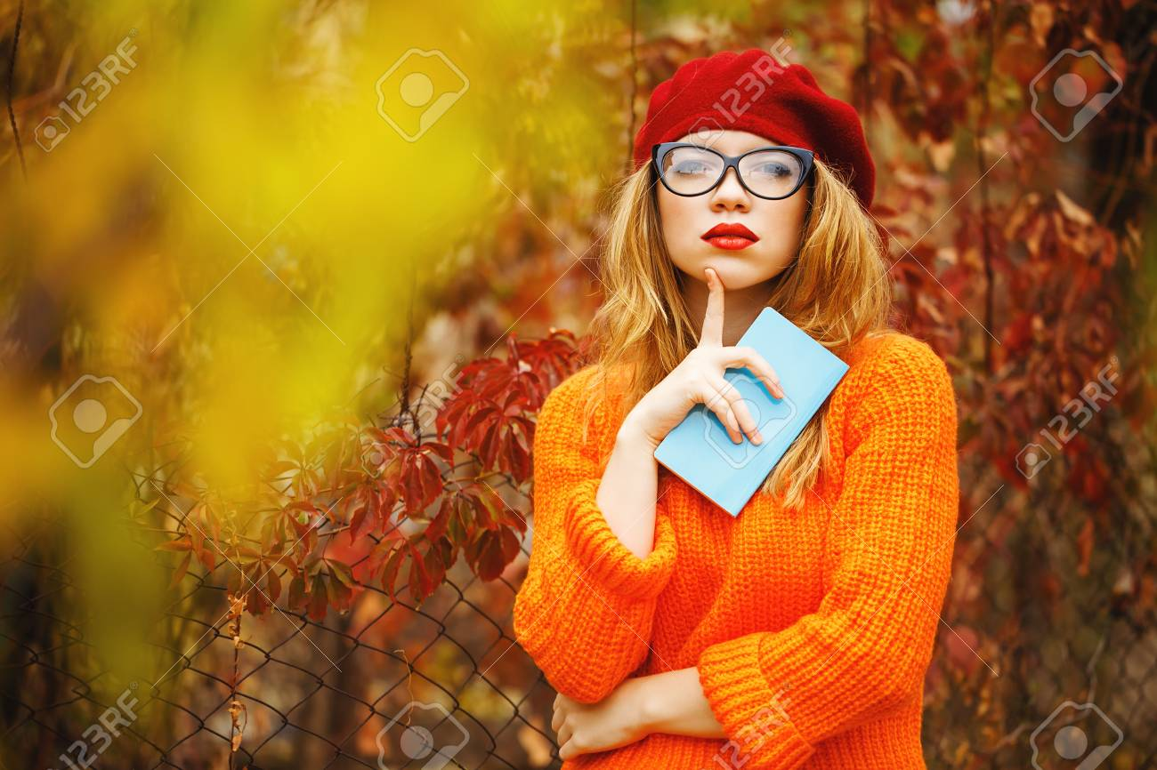 Lovely girl in a beret, sweater and glasses walking in autumn park, holding a notebook. The poet seeks inspiration. Girl enjoying fresh air. The girl white smile. The concept of modern youth fashion. - 47880306