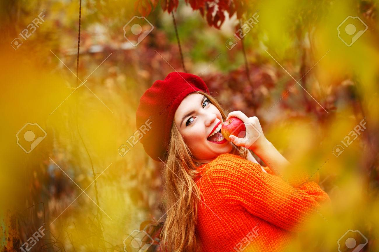 Pretty girl in a beret and a sweater in autumn park, holding a ripe apple and smiling. The girl bites ripe apple. The girl white smile. The concept of healthy teeth. - 47880331