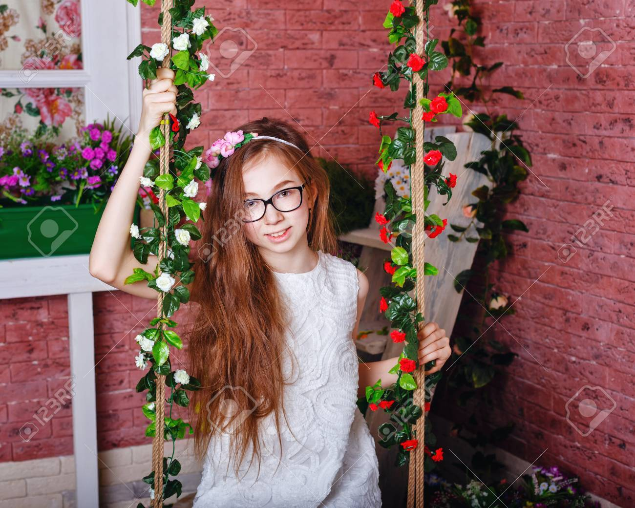 Cute teen girl in glasses sits on a swing. Seesaw decorated with flowers.  Stock