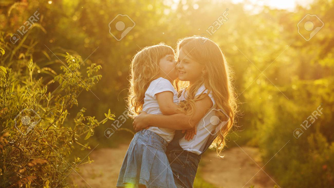 two cute little sisters big hug and kiss in the park on a sunny