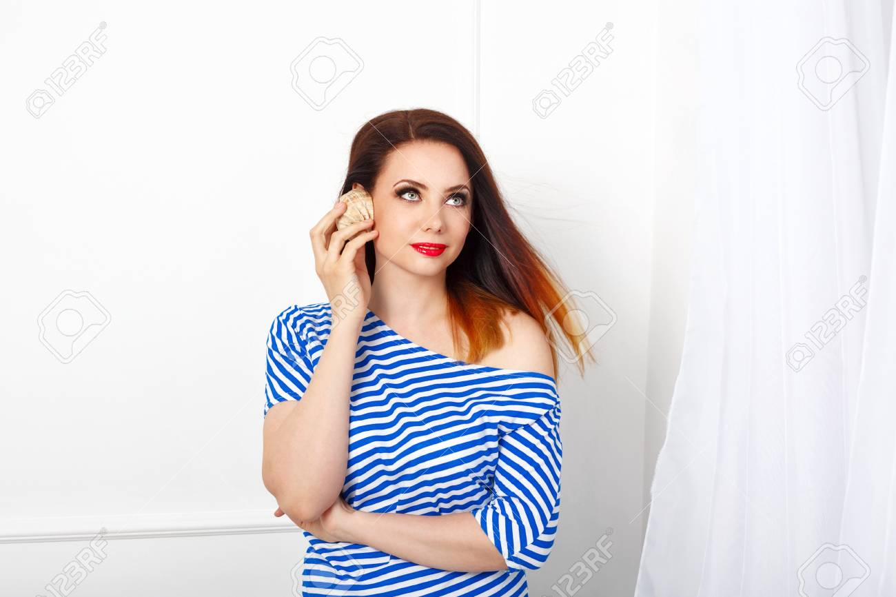 a29a6598e670 Archivio Fotografico - Giovane ragazza attraente tenendo le mani nel  guscio. È vestita in un vestito da marinaio. Voglia di mare.