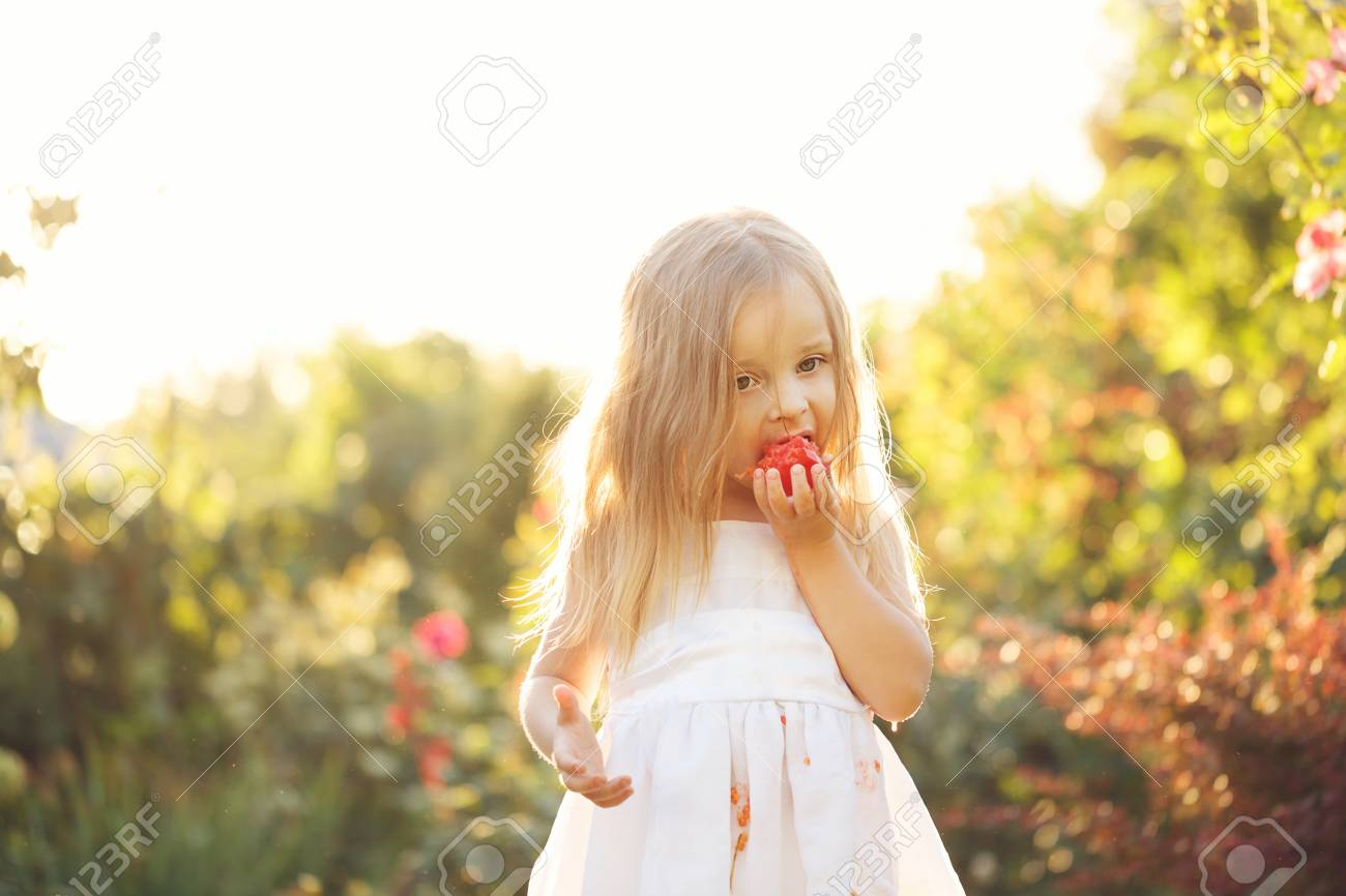 01ee1cc9d2e Girl soiled white dress in tomato juice. Nice little girl eating a tomato.  She stands barefoot on the green lawn. Girl