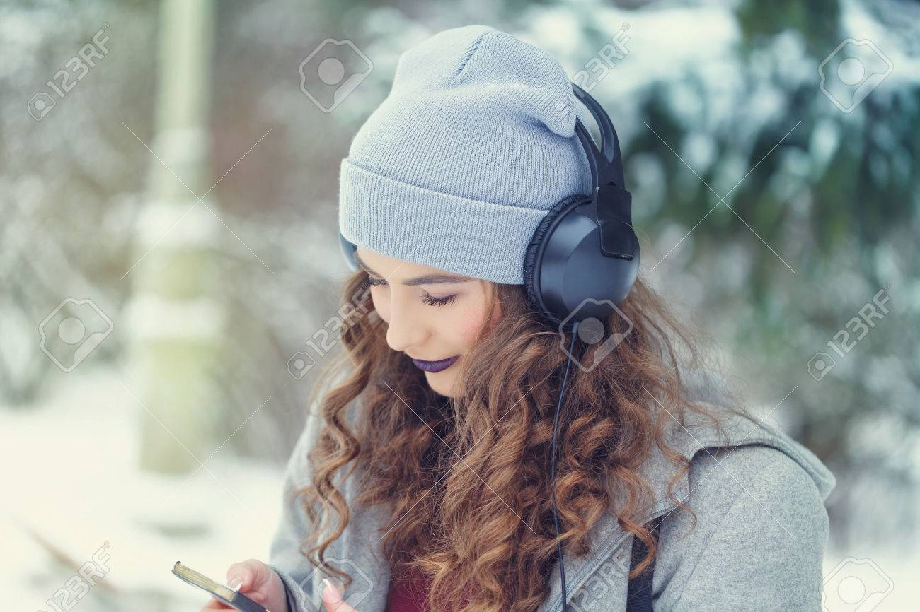 Portrait of pretty attractive girl hipster winter park. She is listening to music on headphones. Youth street fashion. Winter fun. Walks in the open air. - 65788632