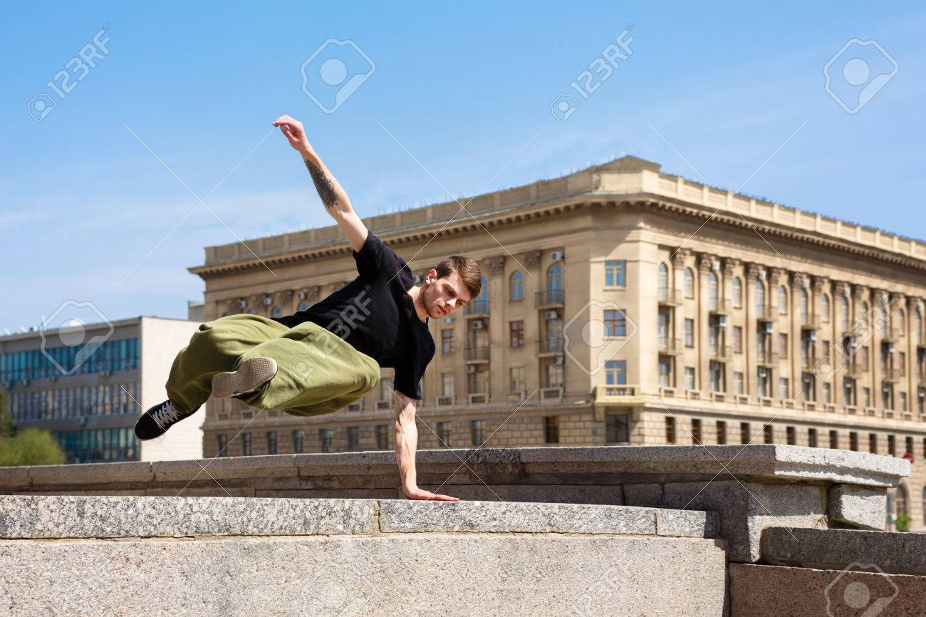 Young man jumping over the wall. Parkour in the urban space. Sport in the city. Sport activity. - 78171851