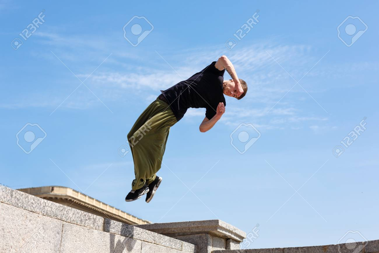 Young man doing a back flip with a turn. Parkour in the urban space. Sports in the city. Sport activity. - 78268122