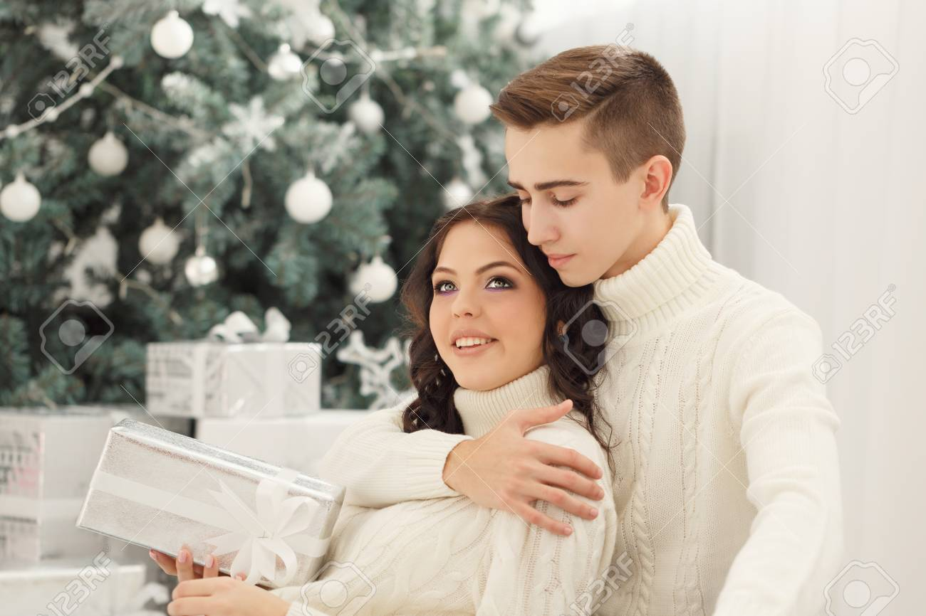 Paar Teenager Zu Weihnachten. Er Umarmt Seine Freundin. Sie Hält Ein ...