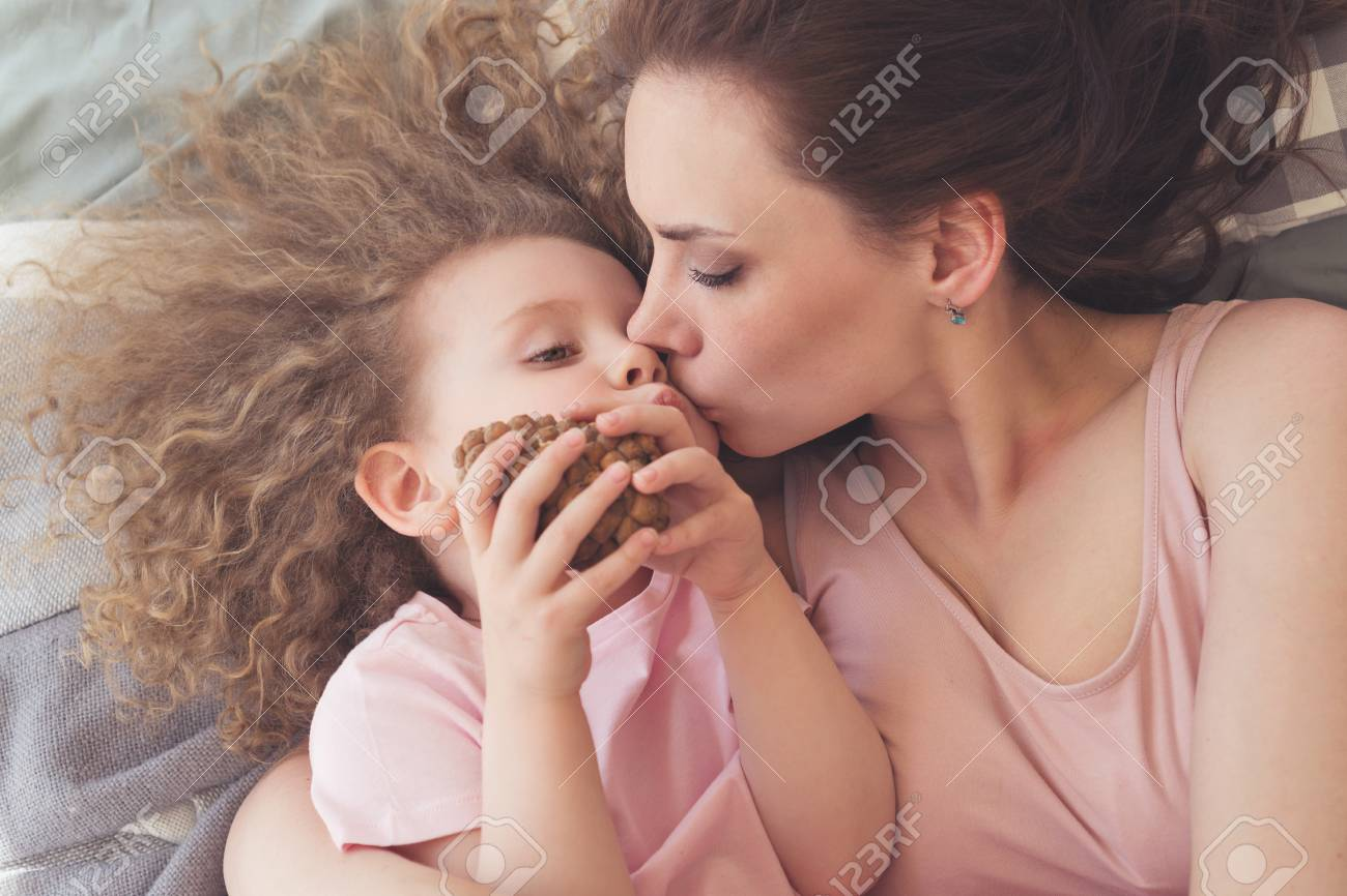 dbde1d4045 Mother hugs and kisses her daughter with curly hair on bed in bedroom