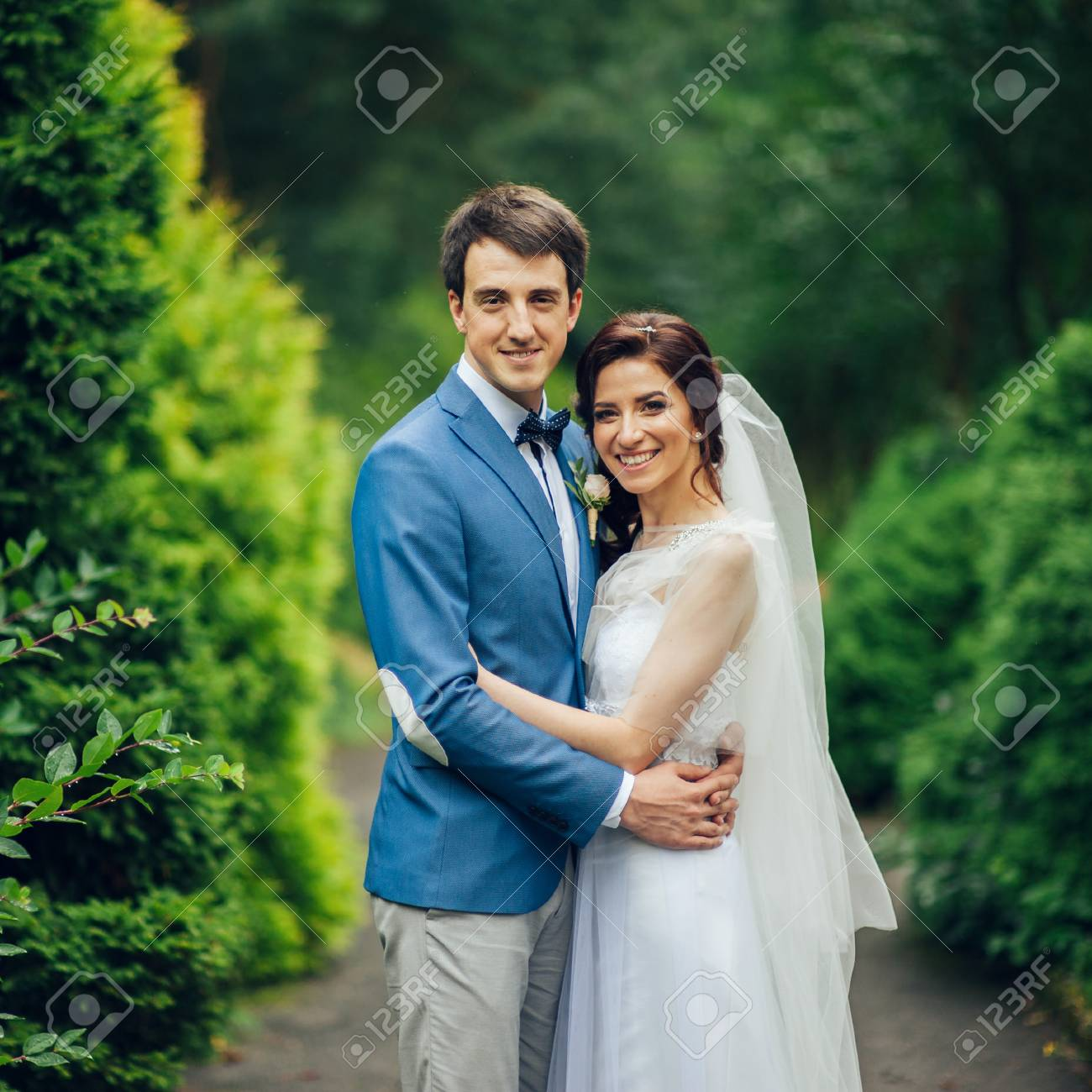Pretty Wedding Couple Poses In A Green Spring Garden Stock Photo Picture And Royalty Free Image Image 93283833