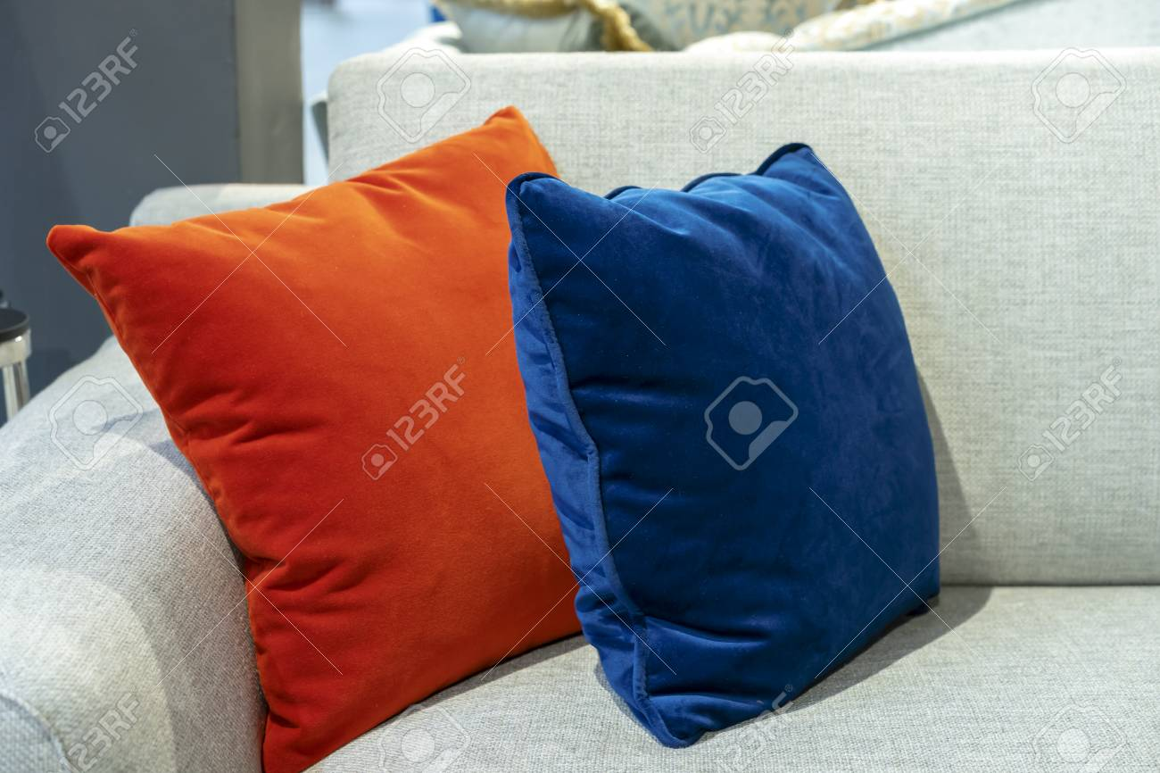 Orange and blue decorative pillows on a beige sofa.