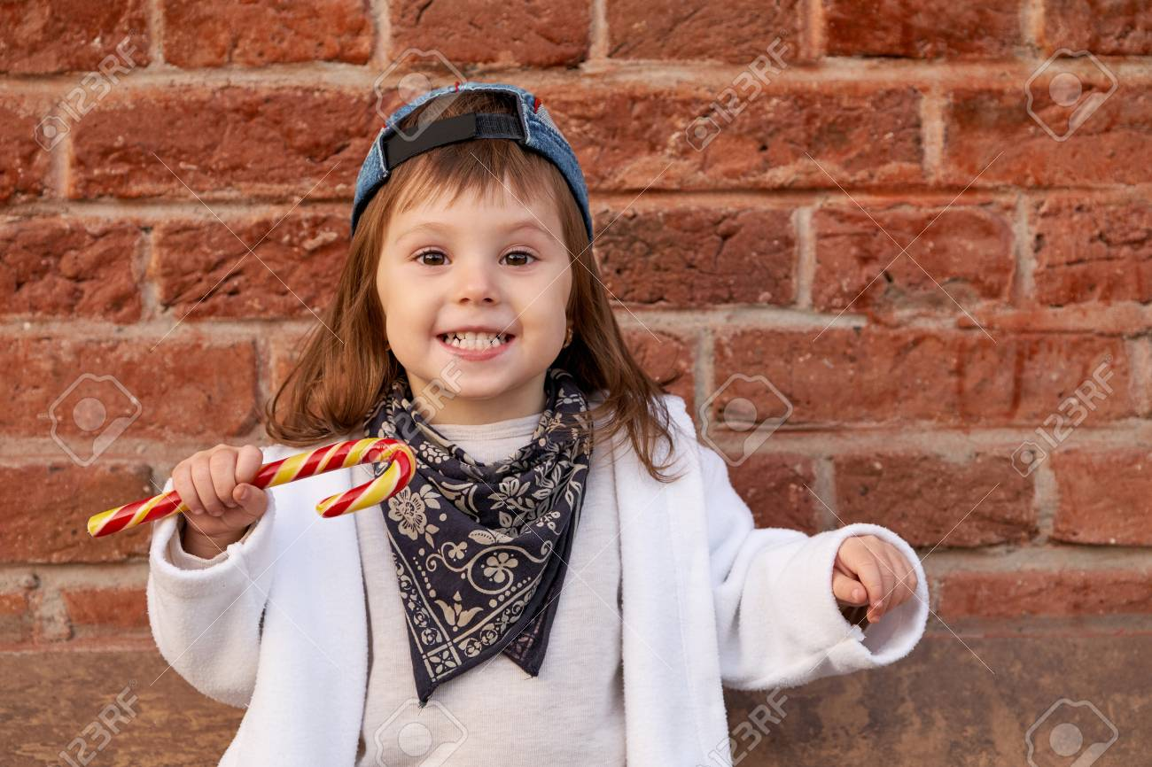 Beautiful cute child eating candies. portrait of cute little girl in the  baseball cap Stock f7d02cbf9048