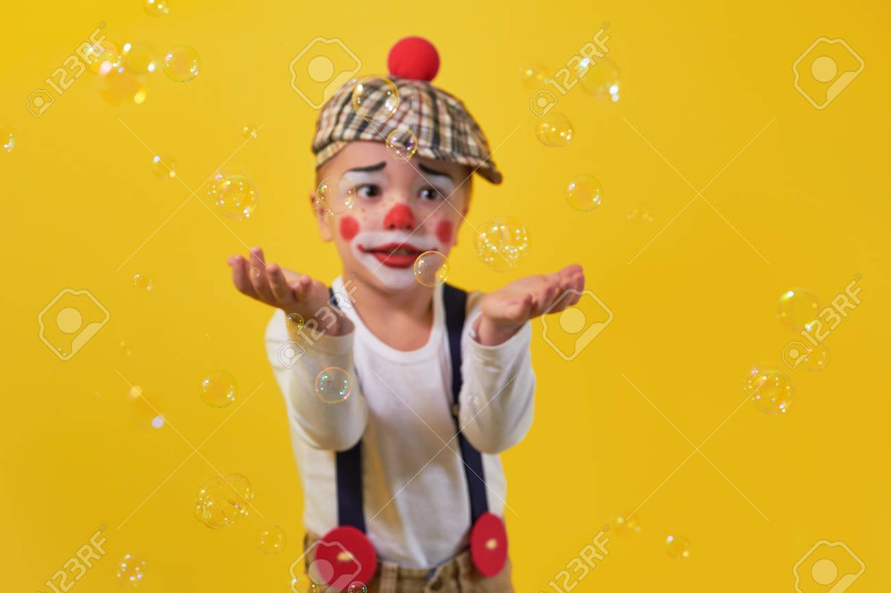 Cute little boy clown in a costume, makeup, catches hands bubbles, soft focus