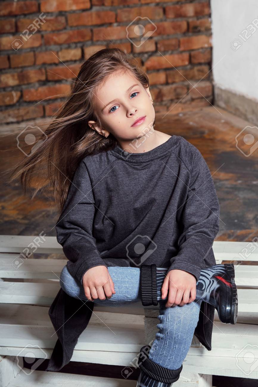 86d40572bf9d7 Portrait little fashion kid. Beautiful child fashion poses. Stylish serious  young girl sitting on