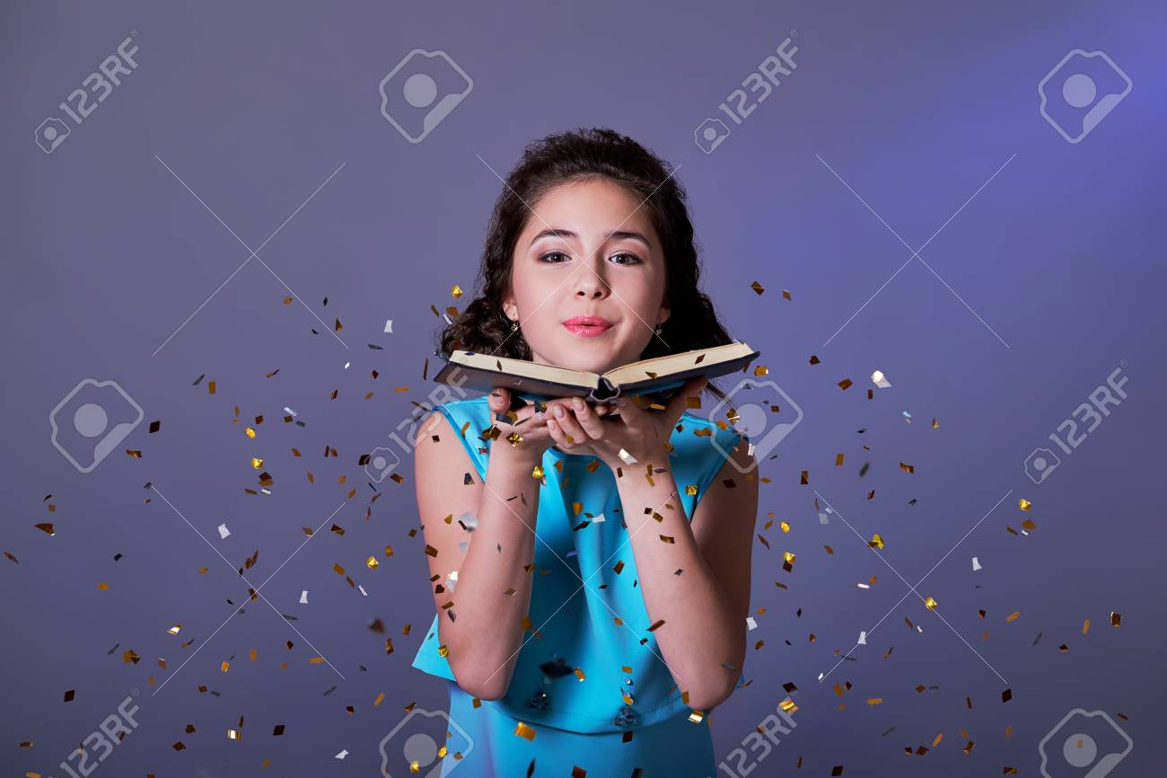 Young woman or teen girl is blowing glitter confetti.Asian girl..