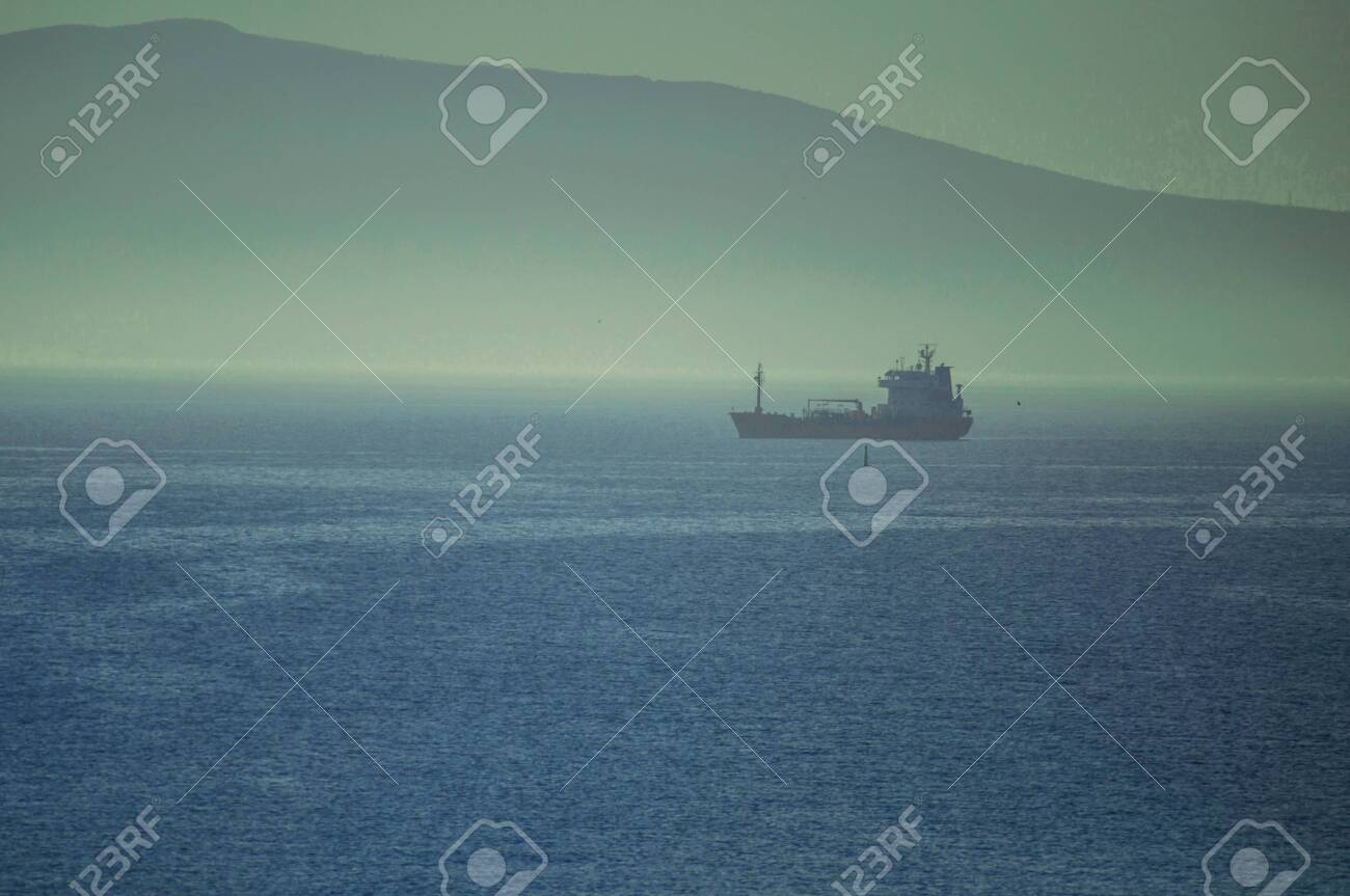 Cargo ships waiting to enter the Novorossiysk port in foggy weather - 122221185