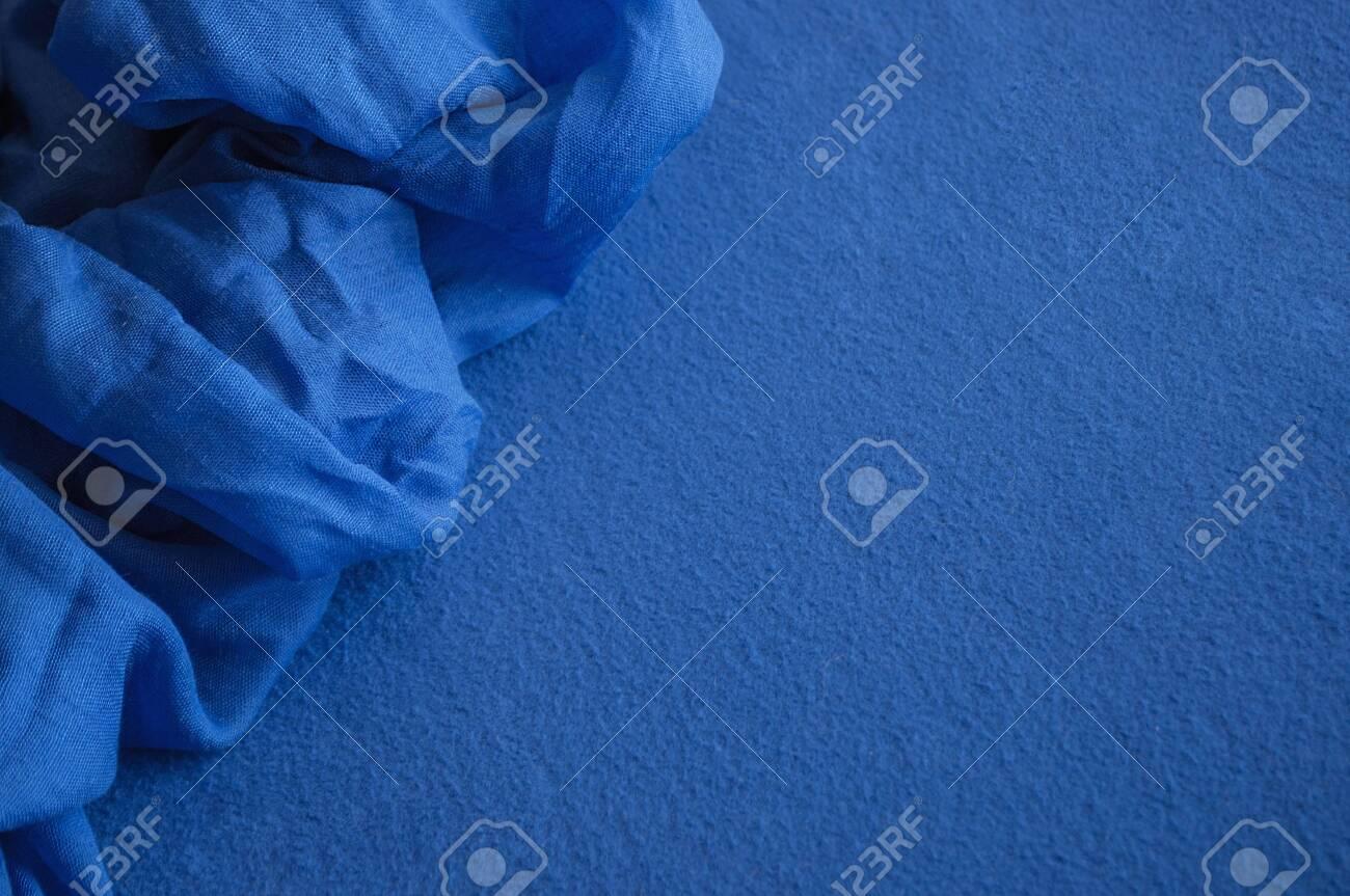 A piece of deep blue lightweight fabric lying on the blue fleece textile. - 124902121