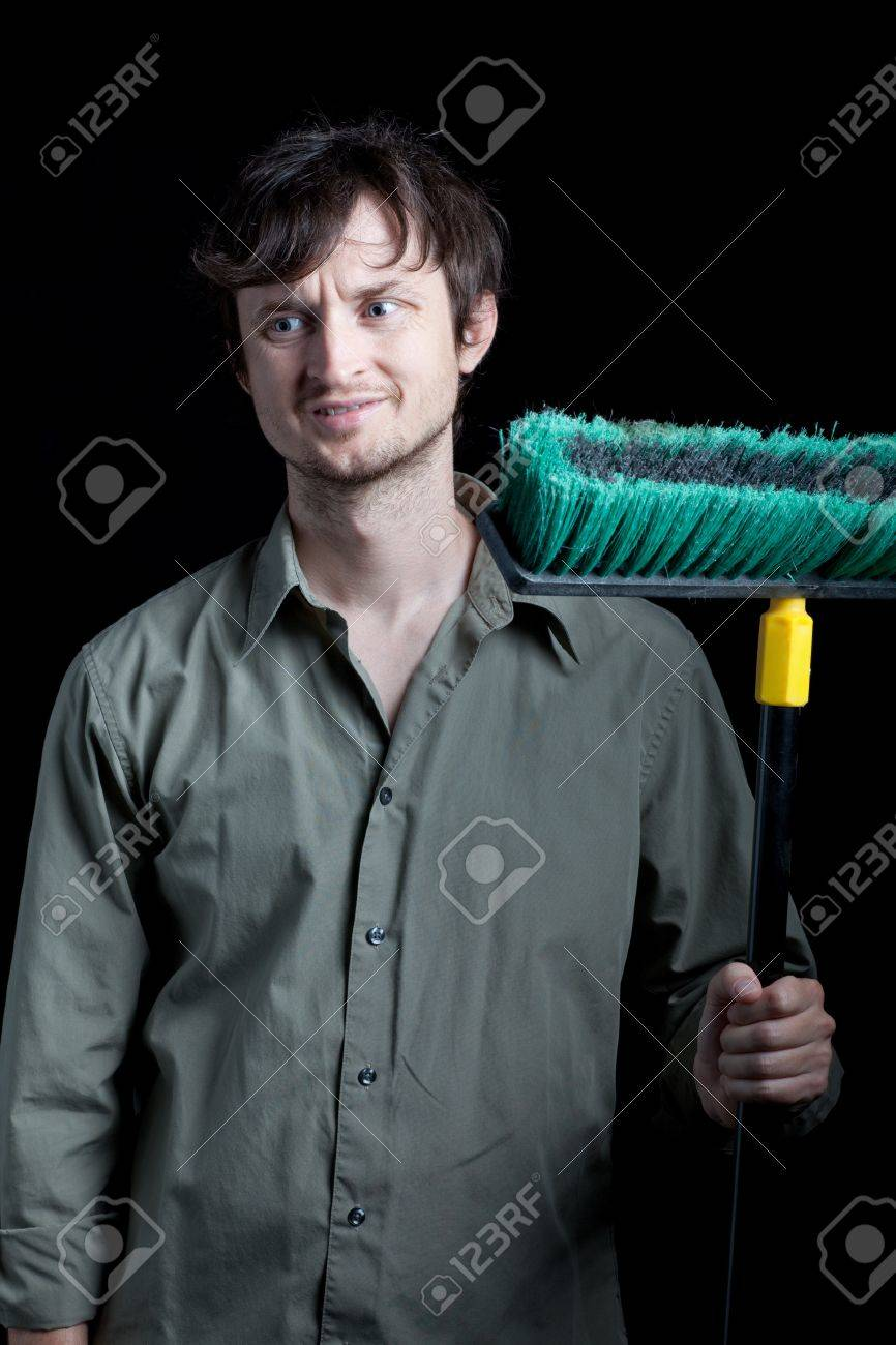 janitor with broom frowning Stock Photo - 9107717