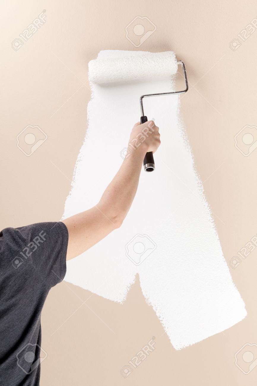 Femme Utilisant Un Rouleau à Peindre Un Mur Blanc Beige