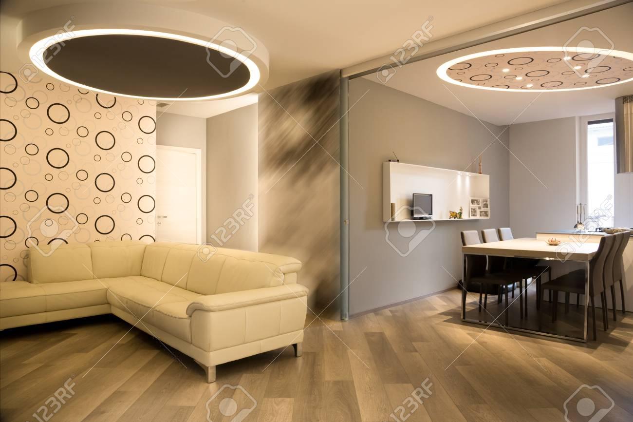 Salon et cuisine modernes séparés par un mur coulissant ouvert, couleurs  chaudes