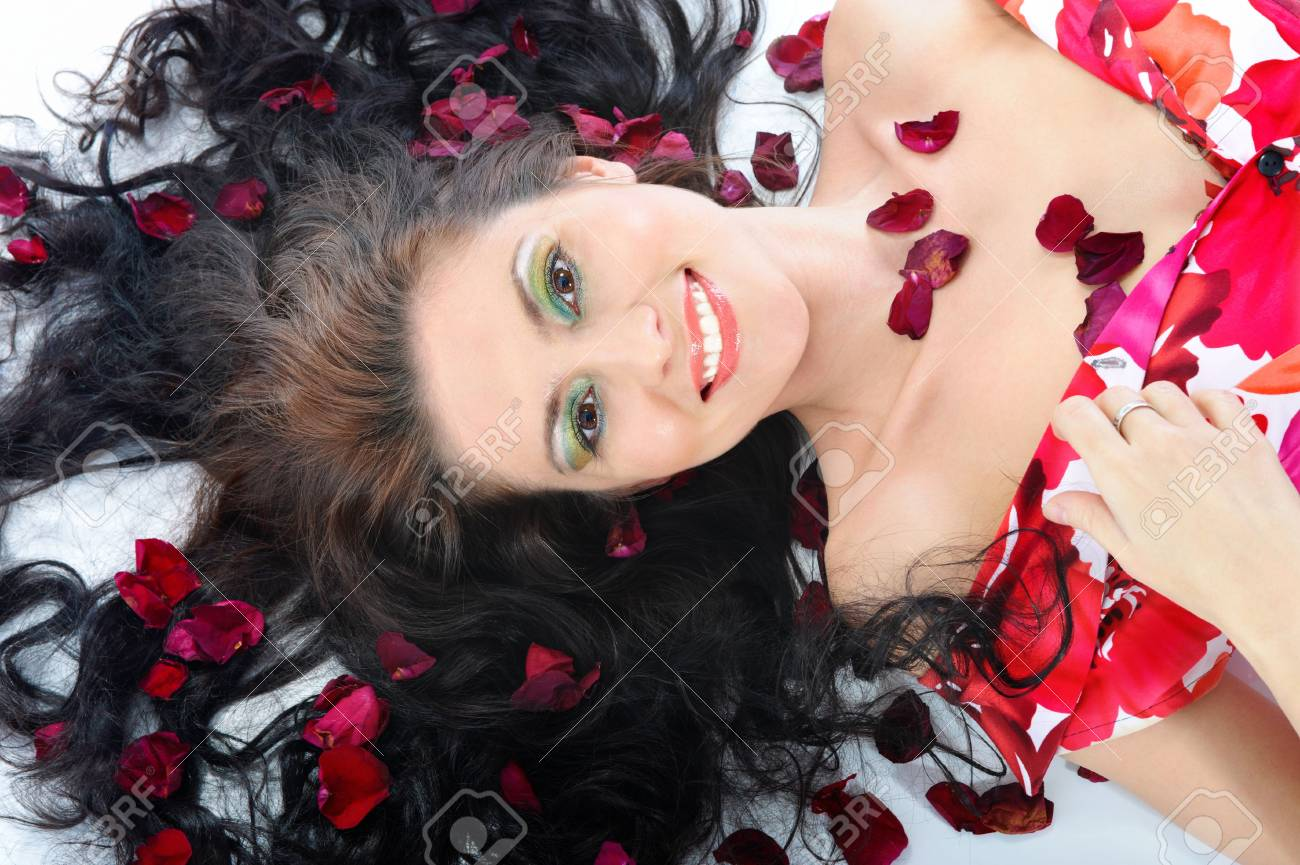 Close-up the smiling young girl lies in petals of roses Stock Photo - 6820470