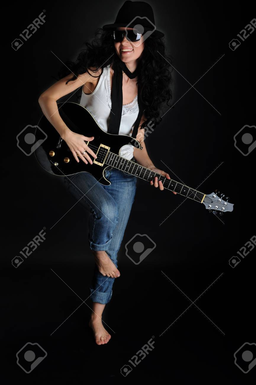 Portrait of a beautiful smiling girl with a guitar in his hands on a black background Stock Photo - 6883117