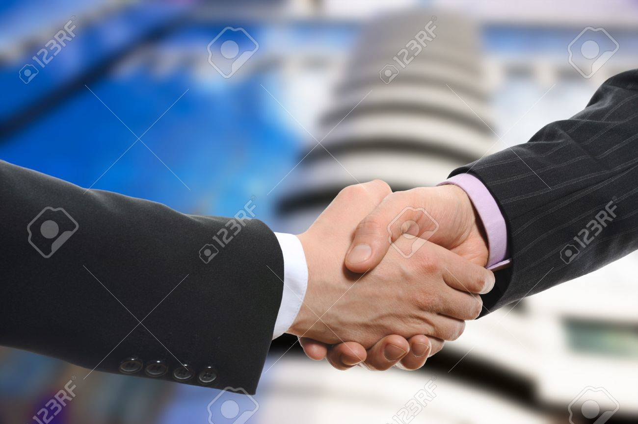 Handshake of two men in black suits on the background of the business building Stock Photo - 7227765