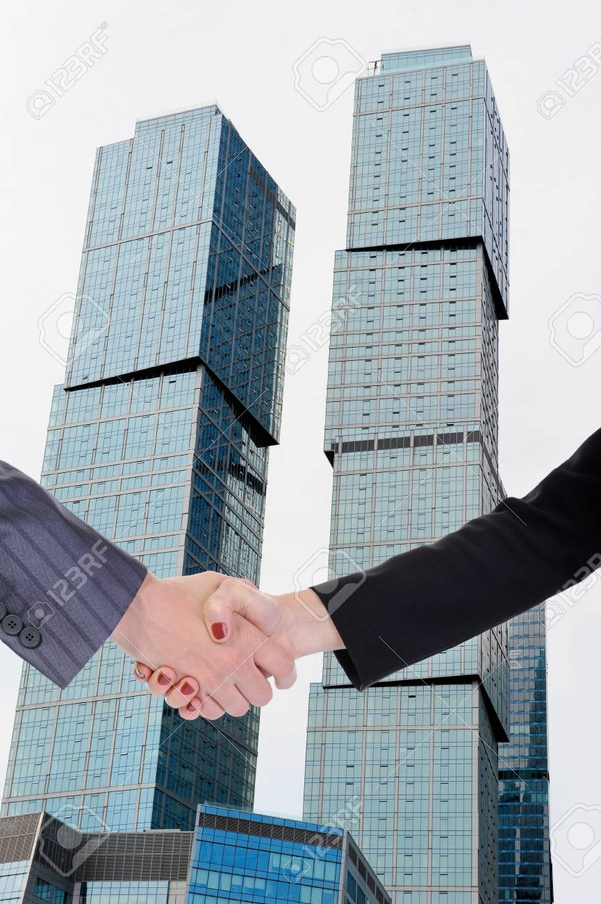 Handshake men and women against the background of the business building Stock Photo - 7364950