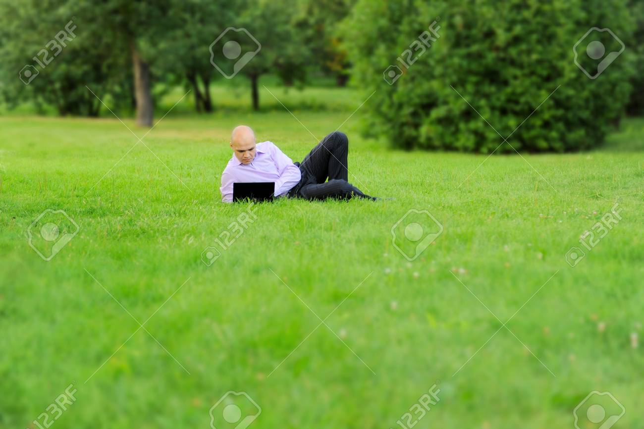 Businessman with laptop lying on green grass in the park Stock Photo - 7539642
