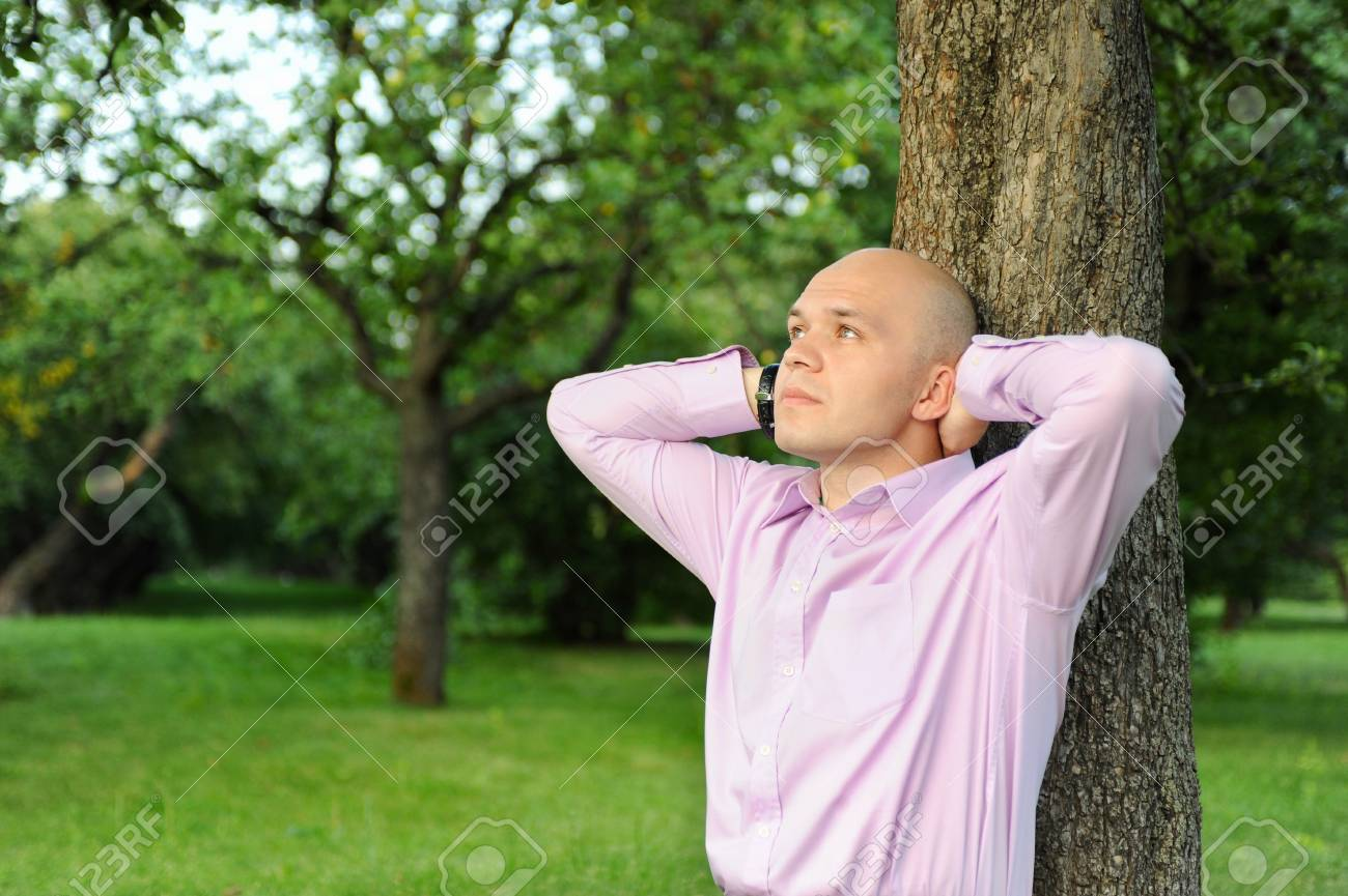man in a green park talking on the phone Stock Photo - 7890746