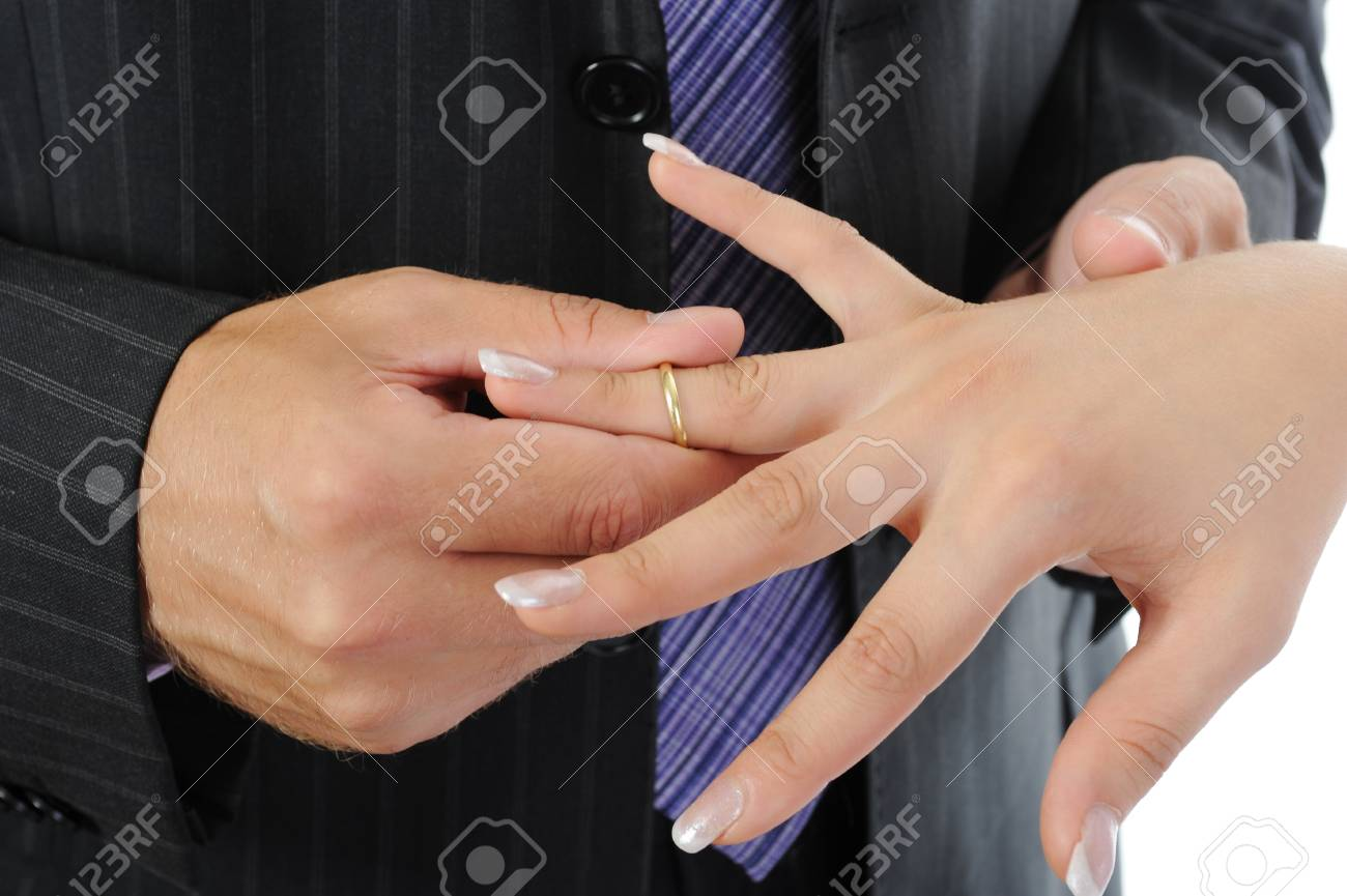 groom wears gold ring bride. Isolated on white Stock Photo - 7905816