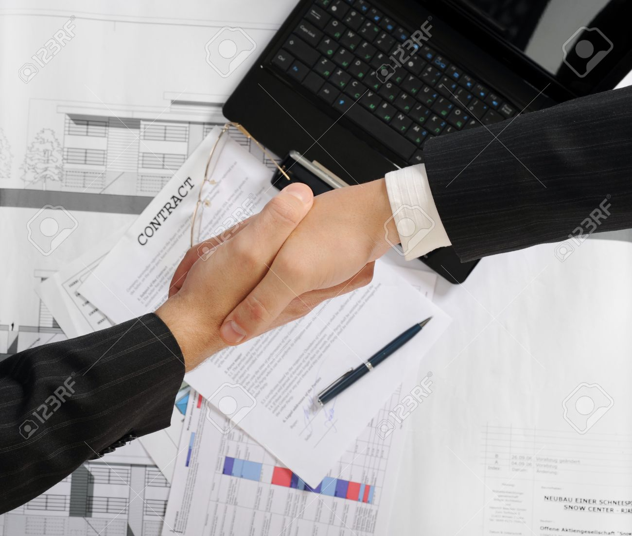 Handshake of two business partners after signing a contract. Focus on the documents Stock Photo - 8133728